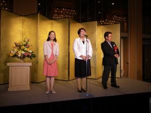 レセプションであいさつする高橋ちづ子と小池あきら副委員長(右)、吉良よし子参院議員(左)。